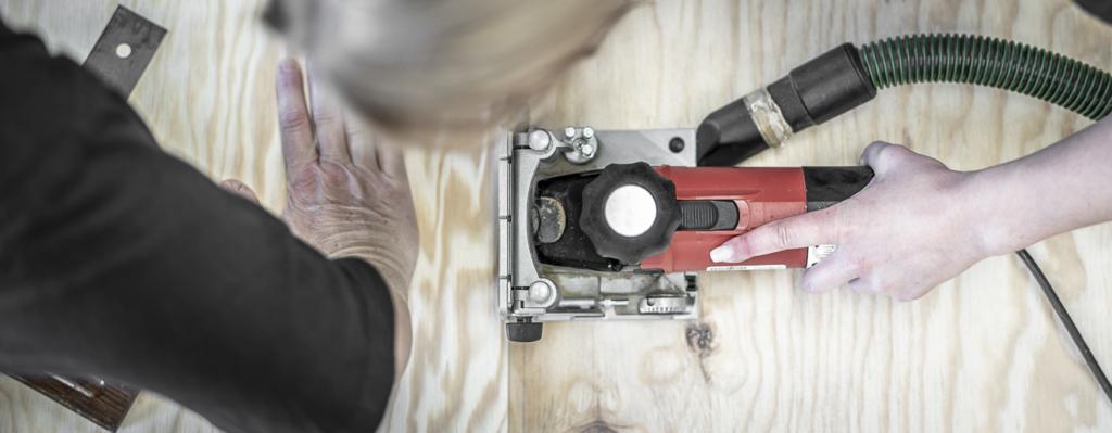 junge Frau bearbeitet mit der Lamellofräse Schichtholzplatten aus Seekiefer in der Holzwerkstatt