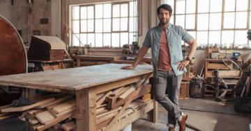 Porträt eines selbstbewussten jungen Holzarbeiters, der in seiner Werkstatt neben einer Holzbank steht